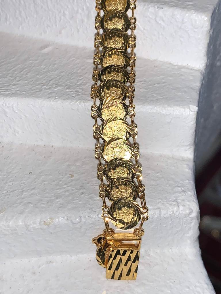 21 karat gold bracelet with small coins that are stacked. These coins are stamp our coins not the actual american coin.