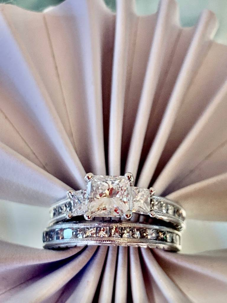 Custom by Z diamond engagement ring from N.J. Diamonds Dearborn. Ring has a princess cut diamond with two princes cut diamonds on either side of the center stone. matching band all done in white gold.